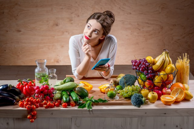 Young woman uses smartphone to track food calories.