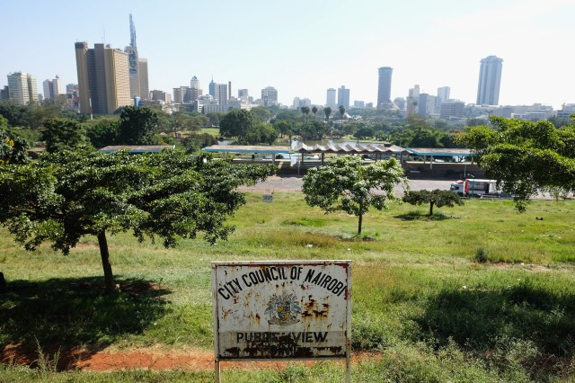 A rusty signboard for Nairobi city in the foreground with a vast green park with trees behind it and the cityscape in the distance with high-rise buildings.