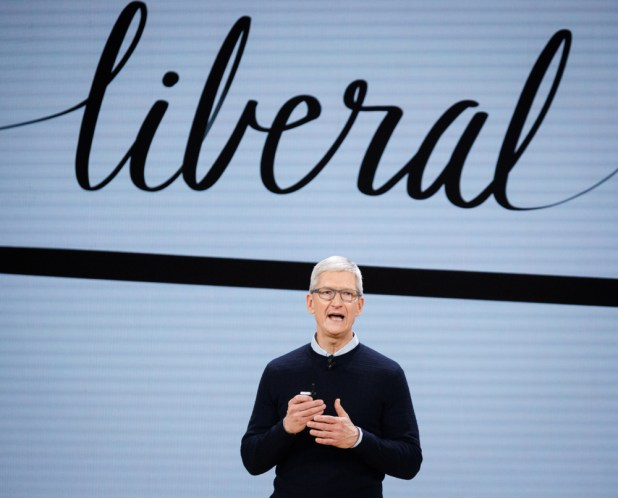 Tim Cook standing below a sign that says 'liberal'