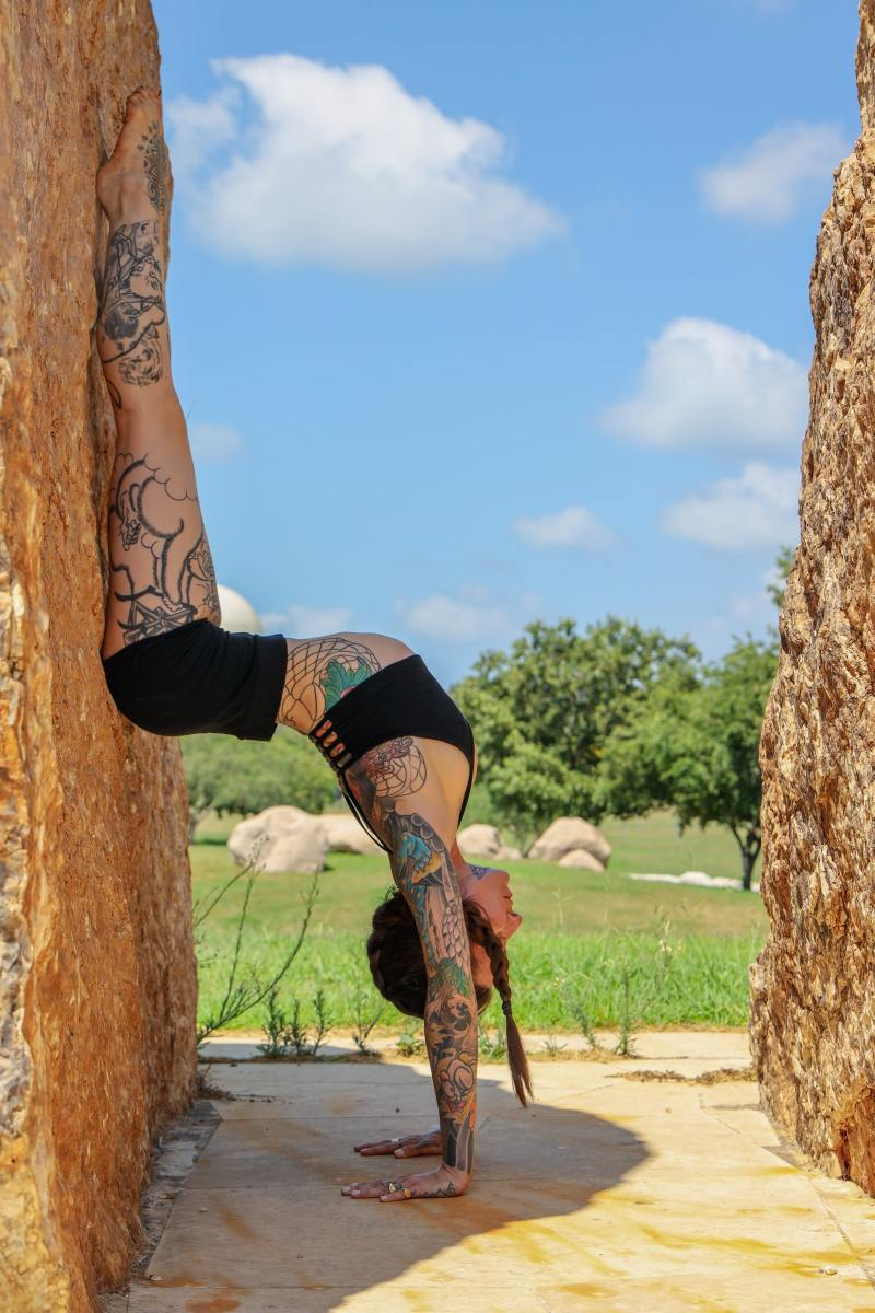 Tattooed girl doing a handstand against a wall