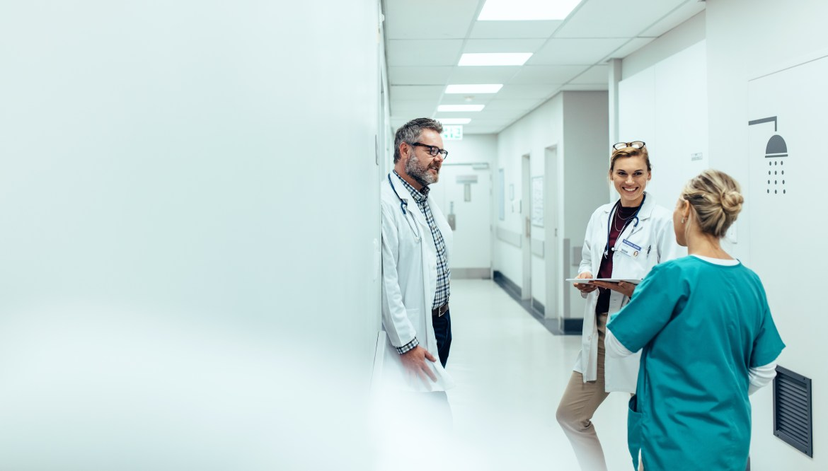 Two doctors and a nurse talk to each other in a hospital hallway.