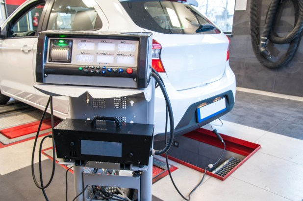 A passenger car in a testing facility with cables attached to the exhaust and a monitor displaying emissions data.