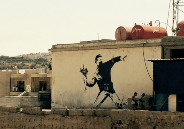 White wall showing Banksy's Flower Thrower, which shows a masked youth throwing a bunch of flowers instead of a rock or a Molotov cocktail.
