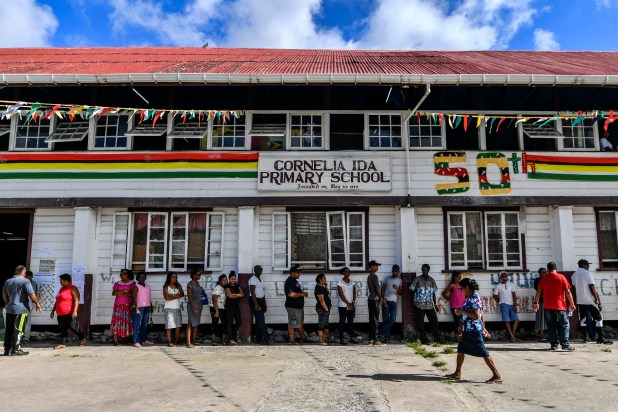 Line of people standing outside a colorfully painted school