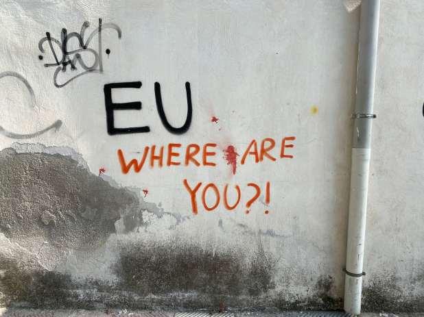 Graffiti reading 'EU, where are you?' on a white wall.