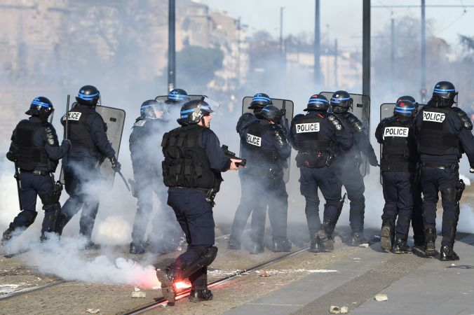 French riot policemen advance during clashes with protesters