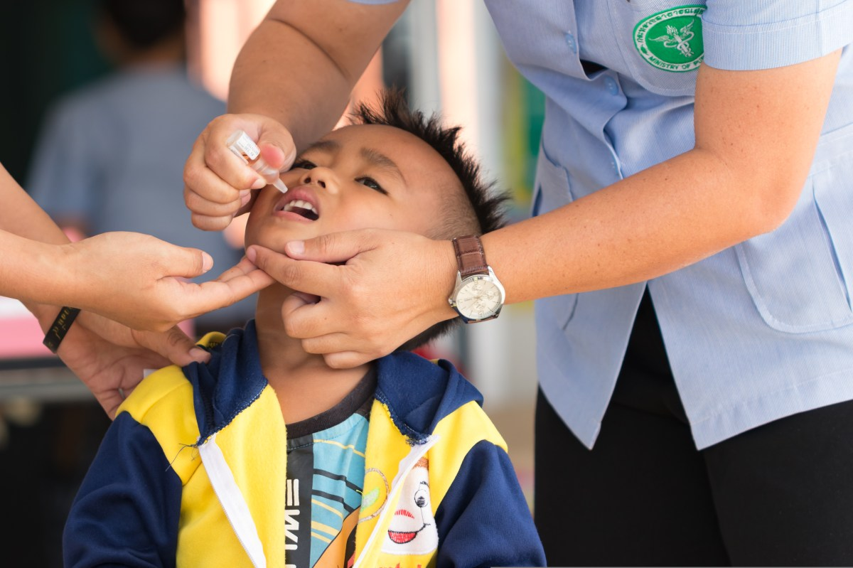 A health worker drops an oral polio vaccine into a child's mouth.