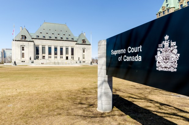 The Supreme Court of Canada in the background and signage in the foreground