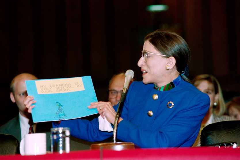Ginsburg holds up a blue piece of paper with a child's drawing reading, 'My grandma is very special' written on it