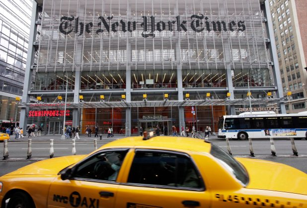 A glass building - with The New York Times written across it. In the foreground, a yellow cab.
