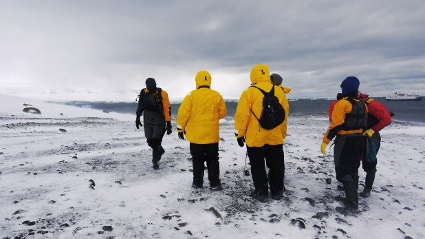 Six tourists standing on ice with their backs to the camera
