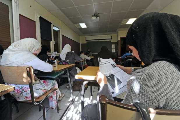 Pupils in headscarves sit at desks