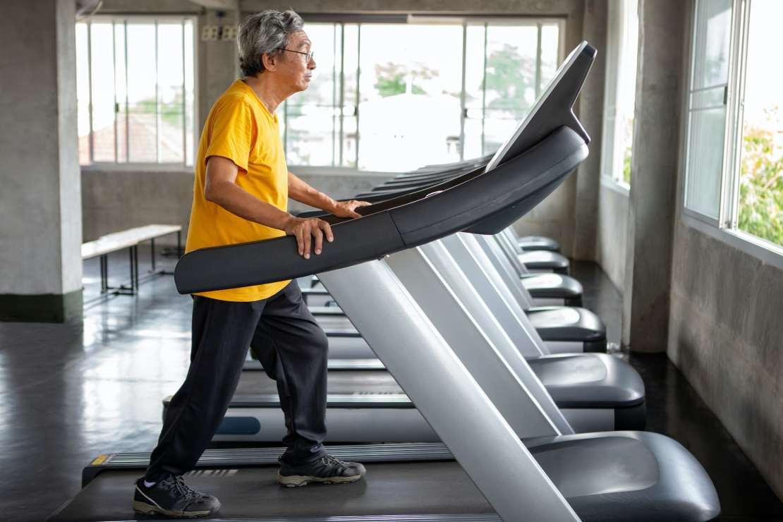 Older man walking on a treadmill.