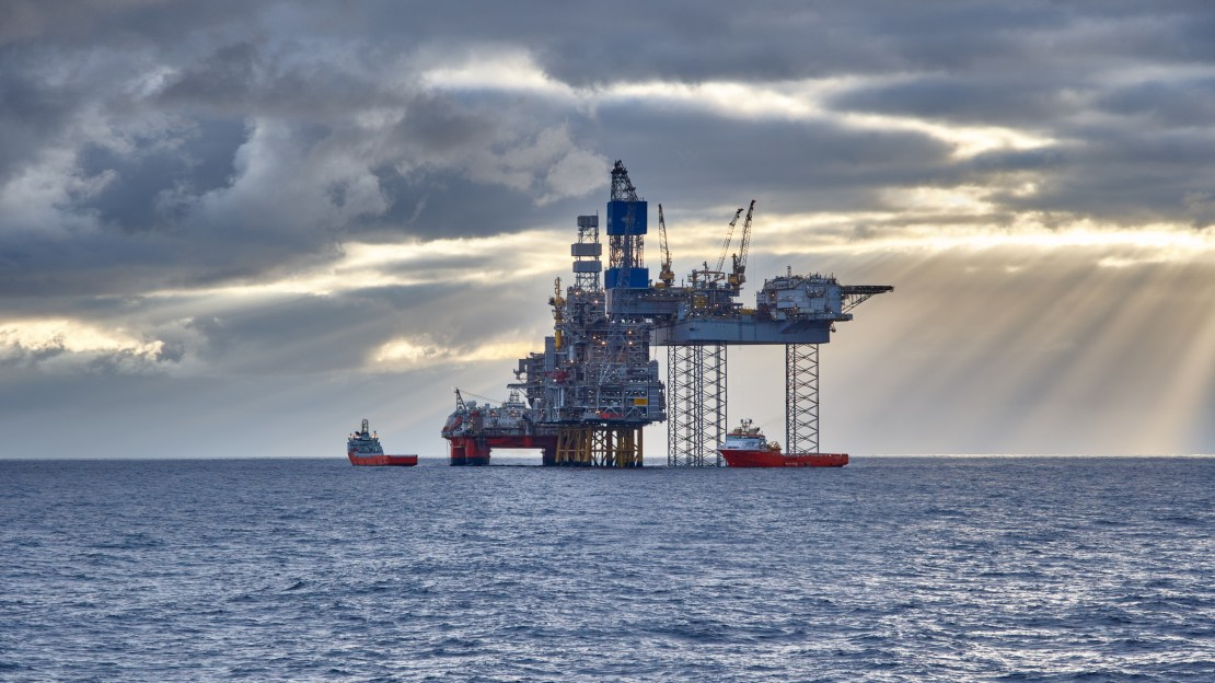 An oil rig in the North Sea with the sun streaming through the clouds over choppy water.