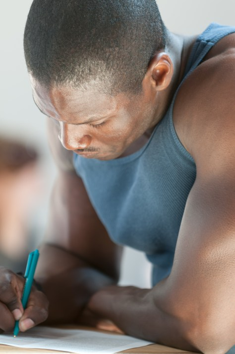 Black man concentrates while completing a form.