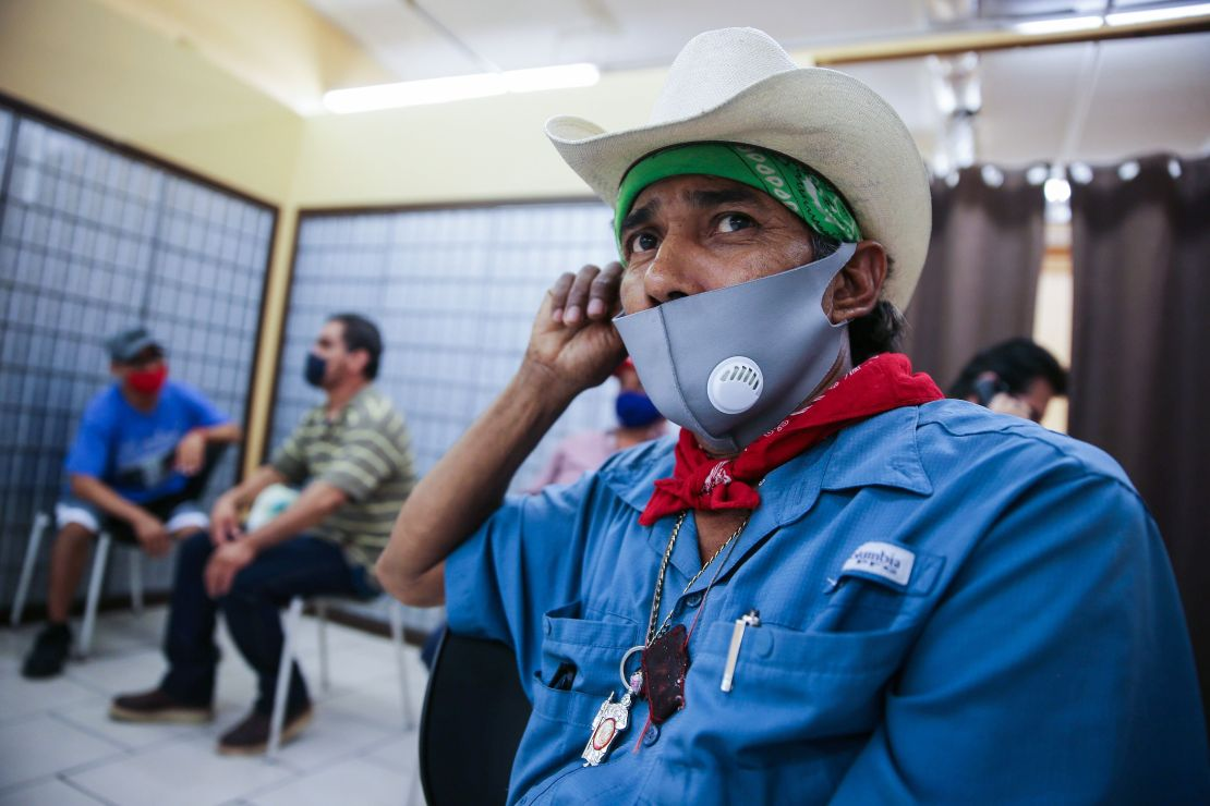 A man partially wearing a mask waits for an employment interview in Imperial County, California.