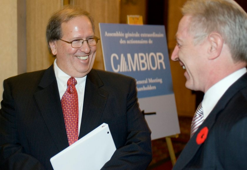 Two men in suits smile as they chat with a Cambior sign behind them.