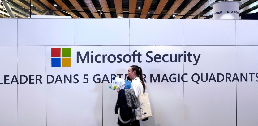 A woman walks in front of the Microsoft stand
