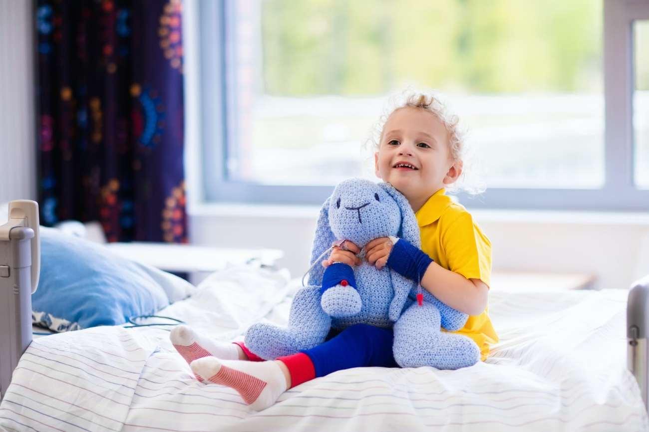 Il giovane bambino felice si siede sul letto di ospedale che tiene un giocattolo del coniglietto blu.