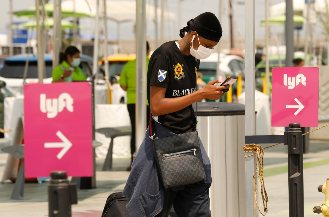 A man checks his phone to locate his Lyft driver at Los Angeles International Airport