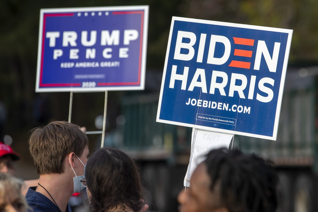 People holding Trump/Pence and Biden/Harris signs.