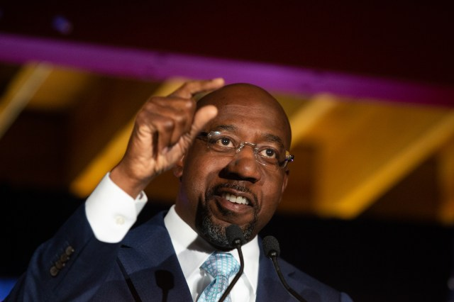 Raphael Warnock points as he speaks during an Election Night event.
