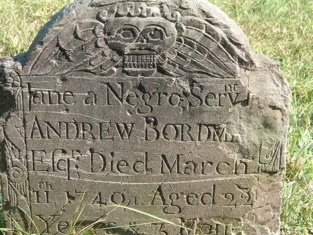 An old grave marker sits in a grassy burial ground