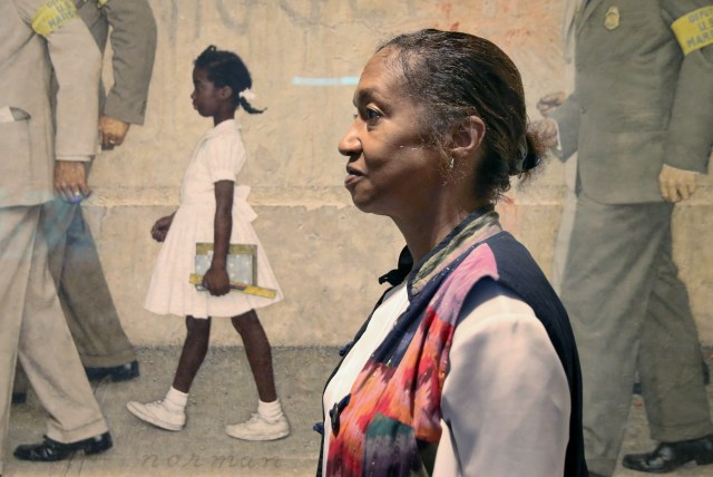 An older woman stands in front of a painting of a young Black girl walking to school