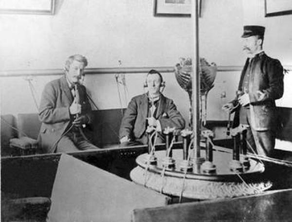 Three men in Victorian England listening to the new Electrophone technology