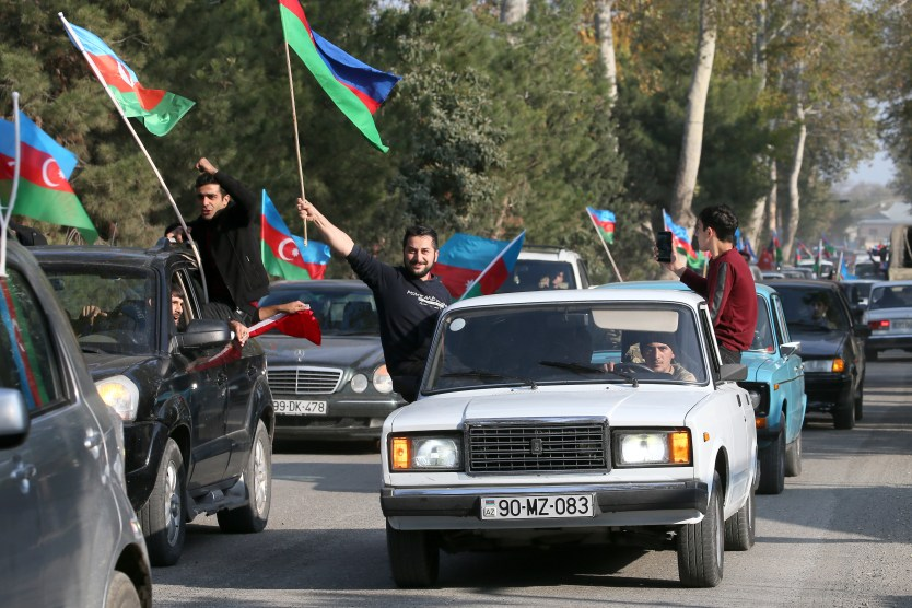 Parade of cars with men waving Azerbaijani flags out the windows