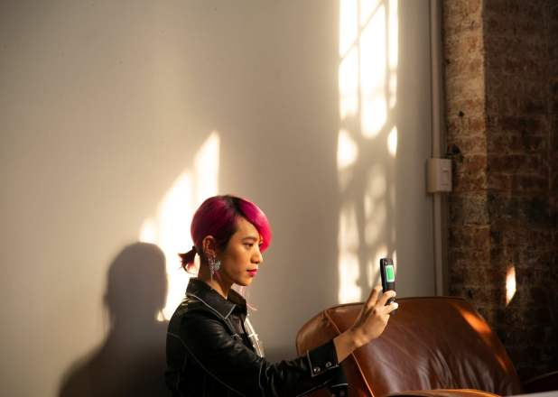 A non-binary person uses their mobile phone at home