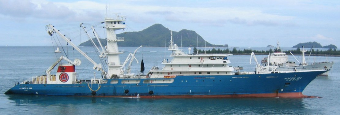 A large blue purse seine trawler with onboard cranes.