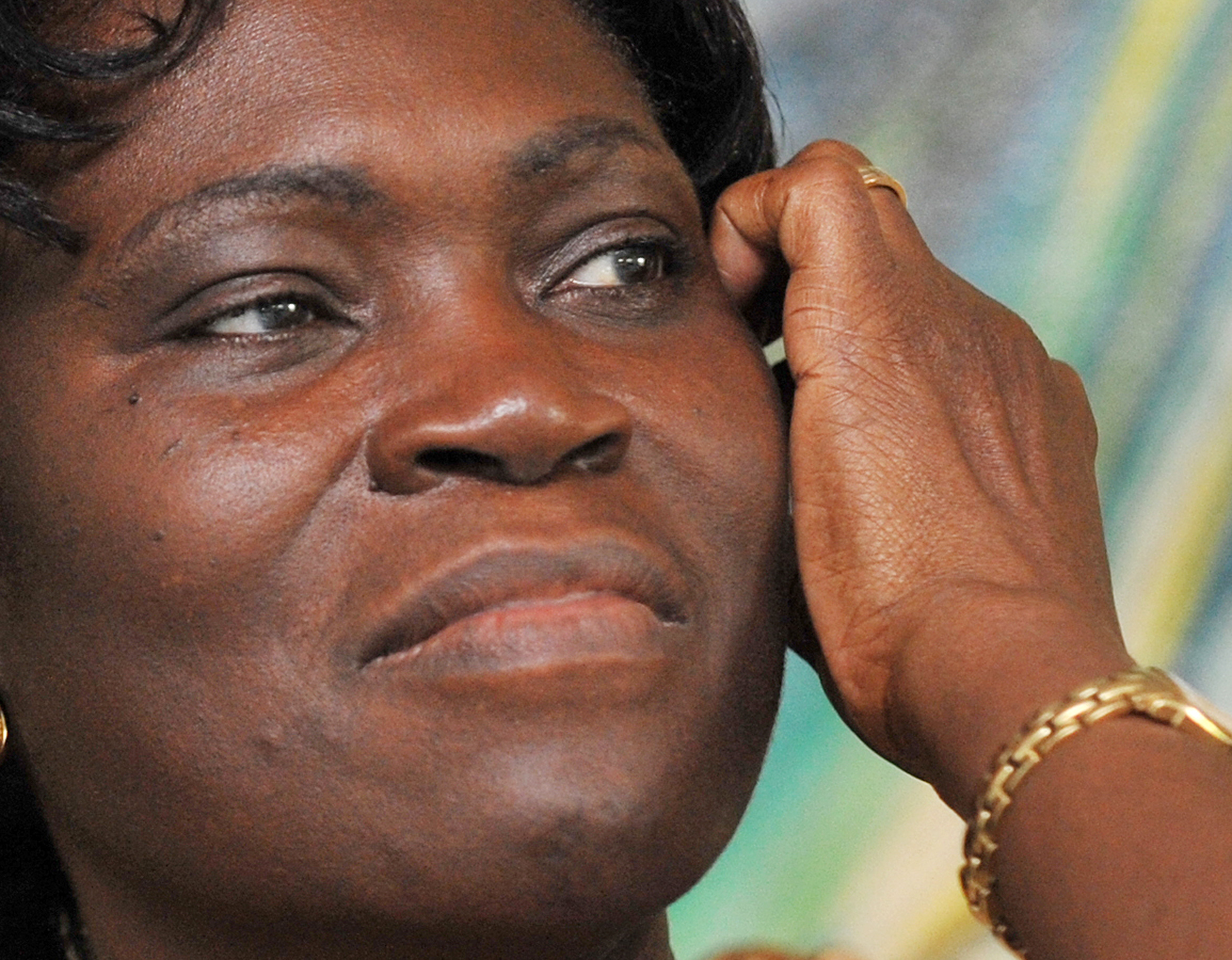 A close-up of Simone Gbagbo shows her scratching her face.