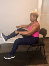 A woman sits in a folding chair, lifting one knee up.
