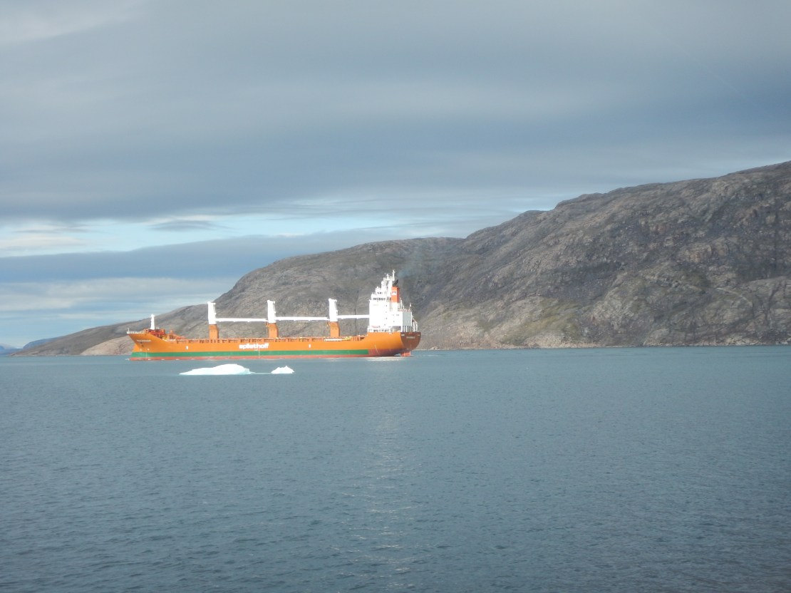 An orange ship sits in icy water with a rocky slope behind it.