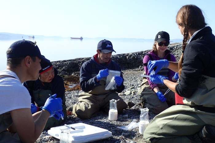 A group of people sit on land and learn how to use sampling devices.