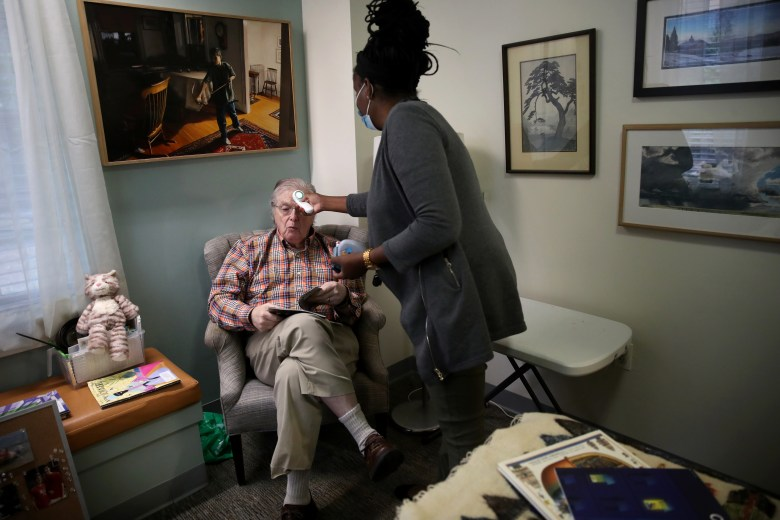 An assisted care facility staff member checks a resident's temperature