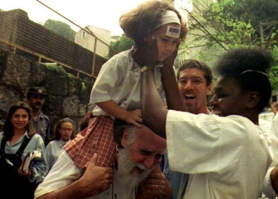 Silva, uma mulher negra, segura uma criança sorridente enquanto uma multidão observa