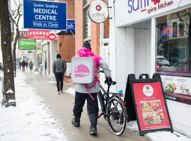 A Foodora courier with a food order on his back pushes his bicycle along a snowy street.