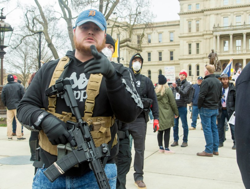 Mannen gekleed in quasi-militaire outfits en met geweren bij een protest in Lansing, Michigan in april 2020.