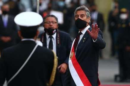Sagasti, wearing a face mask and a presidential sash, waves at the camera