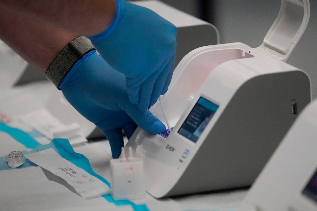 A healthcare worker placing a sample into a the small Abbott ID Now processing machine.