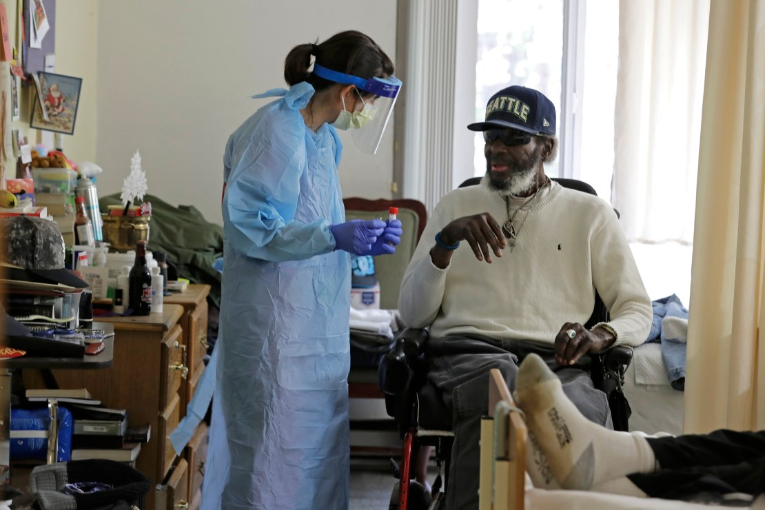 A healthcare worker administering a rapid test to an elderly man.