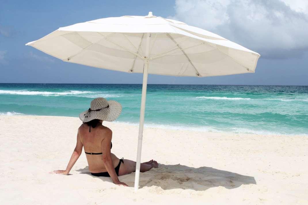 Woman sitting at the beach under an umbrella