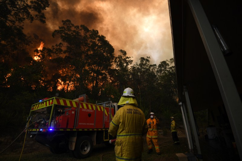 A Fire and Rescue crew worker trying to protect property set alight in NSW.