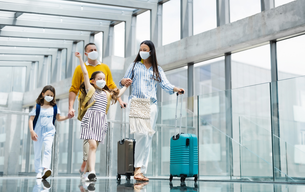 A family of four wearing masks at the aiport