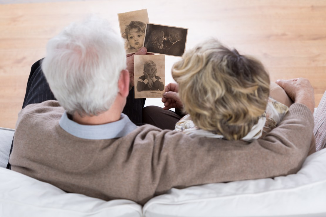 Image of an elderly couple looking at old photos.
