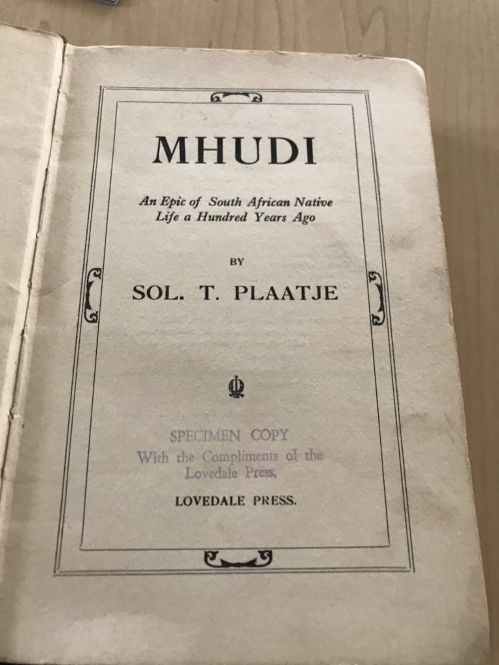 An old book open at the first page, with text in an illustrated frame reading, 'Mhudi - an epic of South African Native Life a Hundred Years Ago.'