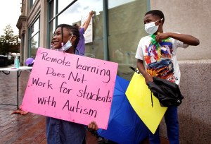 Girl holds handmade poster that reads: 'Remote learning does not work for students with autism'