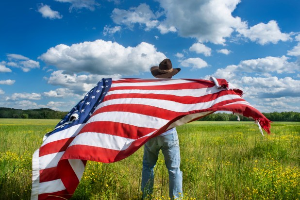A man in cowboy hat holds USA flag and stands in field.